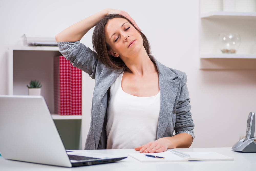 Woman stretching her neck in the office